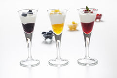 Still life of yogurt, berries, peach and jam. Still life of three cups with yogurt and three kinds of jam (blueberry, peach and strawberry) and decorative Stock Photos