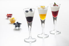 Still life of yogurt, berries, peach and jam. Still life of three cups with yogurt and three kinds of jam (blueberry, peach and strawberry) and decorative Stock Photography