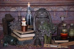 Black Magic Spells. Wiccan spells and herbs. Still Live: Old oil lamps, antique books, dried rose buds, a burning candle in a copper bowl, medicine bottles Stock Photo