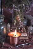 Black Magic Spells. Wiccan spells and herbs. Still Live: Old oil lamps, antique books, dried rose buds, a burning candle in a copper bowl, medicine bottles Royalty Free Stock Photos