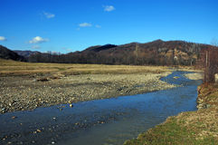 Still mountain river under blue sky stock images