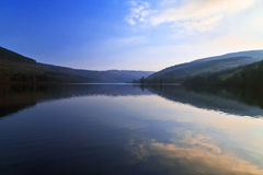 Still and peaceful evening light reflected in Tallybont. Still and peaceful evening light with the forests and mountains of the Brecon Beacons reflected in royalty free stock image