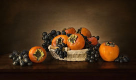 Still persimmons and grapes. In a wicker basket royalty free stock images