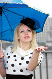 Is it still raining?. Young girl in classic dress is checking if it's still raining Royalty Free Stock Photography