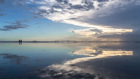 Still reflective sea. Calm water reflects sunset through clouds perfectly. An orange purple blue color. Some boats float in the far distance Royalty Free Stock Photo