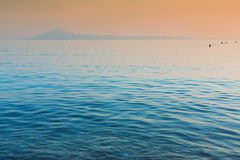 Still sea and distant island. Still calm sea and island at sunset in Thassos Greece Royalty Free Stock Image