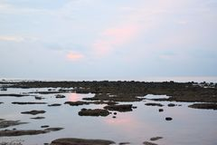 Still Sea Water during Low Tide at Littoral Zone - Pinkish Blue Clear Morning Sky with Reflection in Water - Natural Background. This is a photograph of still stock photography