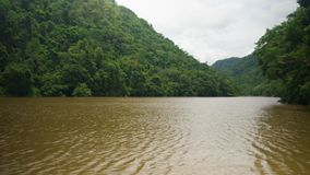 A stream of water in the middle of mountains. A still shot of running a brownish colored stream in between mountains. Green trees surrounds the water stream stock video footage