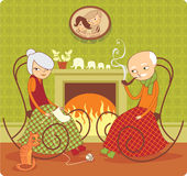 Still together. Elderly couple sitting near the fireside Royalty Free Stock Image