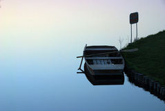 Still water. A boat on still water symbols innocence and honesty, dependability, clearity, aid when help needed. Stands clean against all environmental and Stock Photos