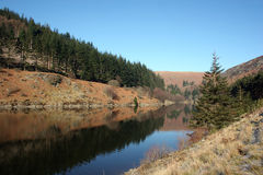 Still Waters at Elan Valley. Still waters in a tree-lined reservoir at the Elan Valley. The still water reflects the deep blue sky royalty free stock image