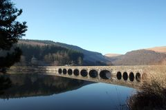 Still Waters at Elan Valley. An arched bridge spans one of the reservoirs at the Elan Valley. The still water reflects the deep blue sky royalty free stock photography