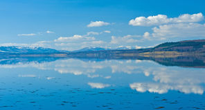 Still waters with strong reflections. An image of the Beauly Firth with the waters so still they are almost a perfect mirror for the clouds and landscape of the Royalty Free Stock Photo