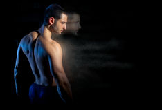 Still Yearning. A handsome muscular man posing on a black background with his soul forging ahead in particles. Shallow depth of field with focus on model's faces Stock Photography