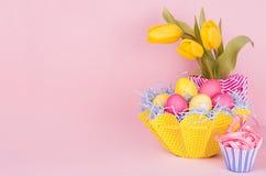 Stilla elegant mjuk pastellfärgad easter garnering - målade ägg, gula tulpan, muffin på rosa bakgrund, kopieringsutrymme royaltyfri bild