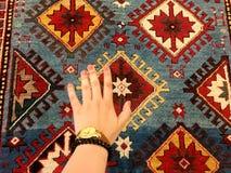 Stilla handen av kvinnan och de orientaliska mattorna Unika modeller Arkivbilder