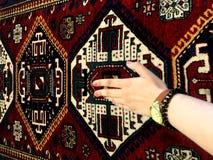 Stilla handen av kvinnan och de orientaliska mattorna Unika modeller Royaltyfria Bilder