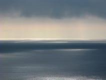 Stilla havet med den klara horisonten, illavarslande moln, patchy reflexioner av solljus arkivbilder