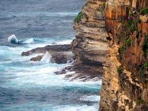Stilla havetvågor som bryter på, vaggar på grunden av klippan arkivbild