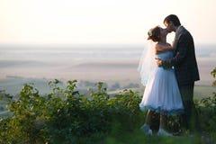 Stilla par som kramar och kysser på bakgrundshorisonten arkivfoto