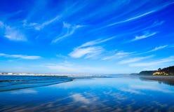 Stillahavs- nordvästlig havstrandshoreline Moln som reflekterar på våt sand Arkivfoto