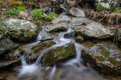Stille rustige stroom die rond grote rotsen stromen stock afbeeldingen