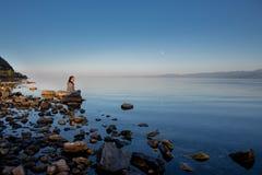 Stille zonsondergang over de rivier Het meisje zit op een grote steen De zomer kalme avond, volle maan stock fotografie