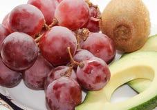 Stilleben av avokadot, druvor och kiwin arkivfoton