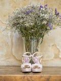 Stilleben av brud- skor och blommor Arkivfoton
