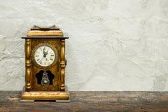 stilleben av den antika klockan woolden på plankan och gammal konkret te royaltyfria bilder