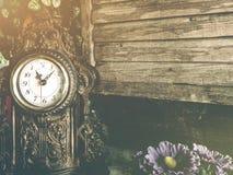 Stilleben av den antika klockan woolden på väggbakgrund Arkivbilder