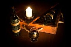 Stilleben av den atmosfäriska gamla träasken med tappningrött vin, exponeringsglas och en stearinljus, låg tangent, utvald fokus royaltyfri fotografi