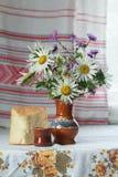 Stilleben av den keramisk vasen och exponeringsglas med klippta lila och vita asterblommor och skiva av yeasted vetebröd Royaltyfri Bild
