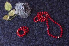 Stilleben av den konstgjorda rosen med röda pärlor och armbandet på textilbakgrund fotografering för bildbyråer