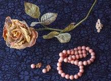 Stilleben av den konstgjorda rosen med rosa pärlor, örhängen, brosch på textilbakgrund royaltyfri bild