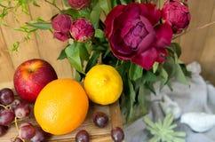Stilleben av den röda pionen blommar med frukt på träbakgrund Royaltyfria Bilder