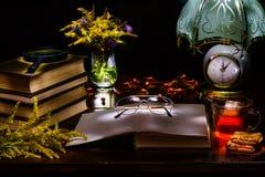 Stilleben av en hög av böcker, exponeringsglas, förstoringsapparaten, vasen med blommor, te och kex, en lampa med en klocka Upply arkivfoto