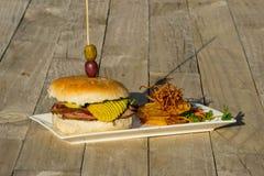 Stilleben av en hamburgare på en platta royaltyfri bild