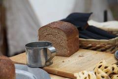 Stilleben av en tenn- kopp och ett nytt bröd Fotografering för Bildbyråer