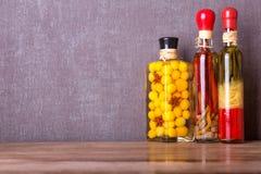 Stilleben av flaskor med olja och grönsaker Arkivfoto