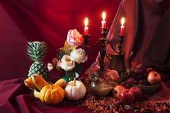 Stilleben av frukter och grönsaken på tabellen och stearinljuset står royaltyfria foton