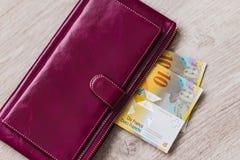 Stilleben av kassa Bordeaux läderplånbok och schweizisk franc på en träbakgrund arkivbild