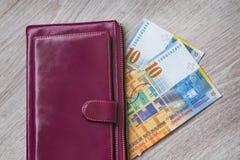 Stilleben av kassa Bordeaux läderplånbok och schweizisk franc på en träbakgrund arkivfoto