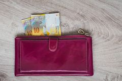 Stilleben av kassa Bordeaux läderplånbok och schweizisk franc på en träbakgrund royaltyfri fotografi