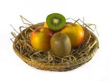 Stilleben av kiwin och äpplet i korgen som isoleras på vit bakgrund Fotografering för Bildbyråer