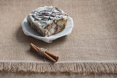 Stilleben av kulinariska kryddor och sötsaker En söt kaka på en vit porslinplatta med kanelbruna pinnar på en brun säckvävsurfac arkivbilder