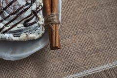 Stilleben av kulinariska kryddor och sötsaker En söt kaka på en vit porslinplatta med kanelbruna pinnar på en brun säckvävsurfac arkivfoto