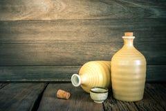 Stilleben av skullflaskor med ljus på wood bakgrund arkivfoto