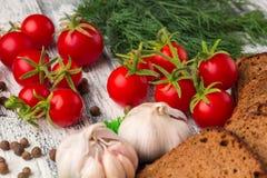 Stilleben av tomater, svart bröd, vitlök, fänkål, bayberry p Royaltyfria Bilder