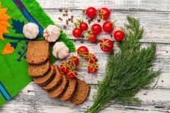 Stilleben av tomater, svart bröd, vitlök, fänkål och peppar Royaltyfri Fotografi